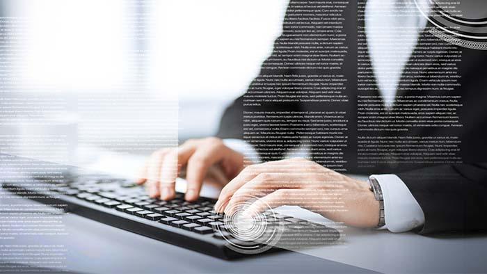 Mann som skriver på pcen og så kommer det mange ord opp på skjermen.
